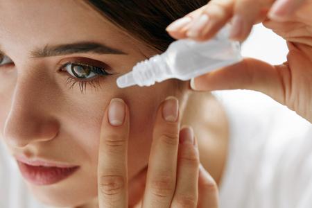 비전 및 안과 의학. 그녀의 눈에 안약을 적용하는 아름 다운 여자의 근접 촬영입니다. 아이의 병을 사용하여 자연 메이크업 젊은 여성 모델은 삭제합니