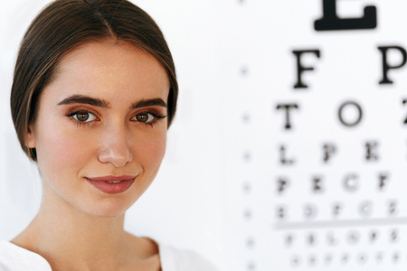 opthalmology: Optometry And Vision. Portrait Of Beautiful Smiling Girl Face At Opthalmologist Office. Closeup Of Happy Young Woman With Healthy Eyes And Visual Eye Test Chart On Background. High Resolution Image Stock Photo