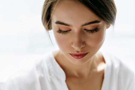 아름 다운 여자 얼굴입니다. 흰색 배경에 아름 다운 갈색 머리 젊은 여자의 근접 촬영. 부드러운 피부와 완벽 한 자연 메이크업 섹시 한 여자의 초상화.