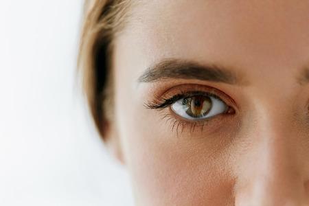 안구 건강 및 관리. 아름 다운 여자 큰 갈색 눈과 눈 썹의 근접 촬영입니다. 소녀 눈 부드러운 건강 한 피부와 완벽 한 자연 메이크업 흰색 배경에 소녀.