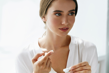 shortsighted: Eyes Health. Portrait Of Young Beautiful Woman With Natural Makeup And Contact Lenses In Hand. Closeup Of Female Model Holding White Lens Box. Eye Care And Healthy Lifestyle. High Resolution Image