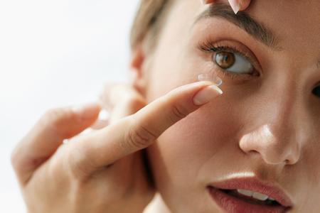 Kontaktlinse für Vision. Nahaufnahme des weiblichen Gesichtes mit dem Anwenden der Kontaktlinse auf ihren braunen Augen. Schönheit, die Augenlinsen mit den Händen setzt. Augenheilkunde Medizin und Gesundheit. Hohe Auflösung Standard-Bild
