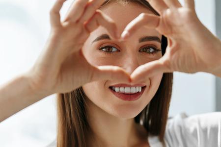 Ojos sanos y la visión. Retrato de mujer feliz celebración de las manos en forma de corazón cerca de los ojos. Primer plano de niña sonriente con la piel sana mostrando la muestra del amor. Cuidado de ojos. Imagen de alta resolución
