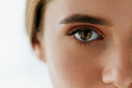 Santé des yeux et de soins. Gros plan de belle femme Big Brown Eye Et Sourcils. Eye Girl lisse peau saine et maquillage naturel parfait sur fond blanc. Image à haute résolution
