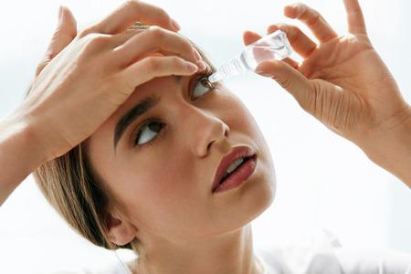 Médecine de la vision et de l'ophtalmologie. Gros plan d'une belle femme qui applique des gouttes d'yeux dans ses yeux. Jeune modèle féminin avec maquillage naturel utilisant une bouteille de gouttes pour les yeux. Concept de santé. Haute résolution