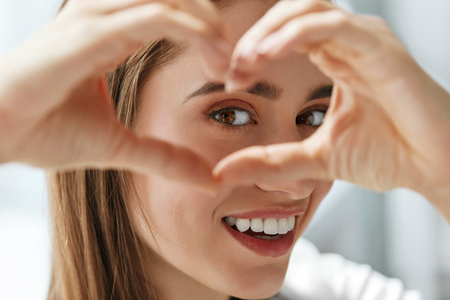 Healthy Eyes And Vision. Portrait Of Beautiful Happy Woman Holding Heart Shaped Hands Near Eyes. Closeup Of Smiling Girl With Healthy Skin Showing Love Sign. Eyecare. High Resolution Image