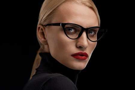 female model: Woman Model In Fashion Glasses. Beautiful Girl With Sexy Face Makeup, Red Lips Wearing Optical Eyeglasses On Black Background.  Female In Cat Eye Design Eyewear Frame. Beauty Concept. High Resolution Stock Photo