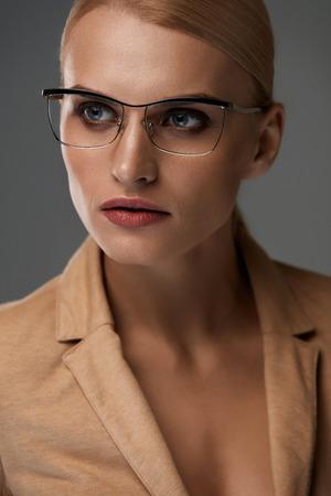 blazer: Womens Eyewear. Beautiful Business Woman With Natural Face Makeup In Beige Blazer Wearing Elegant Stylish Black Optical Eye Glasses,  Fashion Eyeglasses Frame On Grey Background. High Resolution Stock Photo