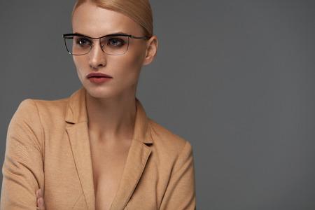 glasses eye: Business Woman Portrait. Beautiful Confident Young Businesswoman Wearing Fashionable Optical Eye Glasses, Elegant Eyewear And Beige Blazer Jacket On Gray Background In Studio. High Resolution Image