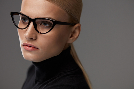 black: Women Eyewear. Beautiful Sexy Young Woman With Natural Face Makeup In Fashionable Stylish Optical Eye Glasses On Grey Background. Attractive Girl Wearing Black Fashion Glasses Frame. High Resolution