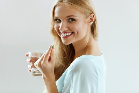 건강한 다이어트 영양. 아름 다운 미소 젊은 여자 복용 비타민 알약의 초상화입니다. 행복한 여자 지주 다채로운 캡슐 먹는 피임약과 유리 민물의의 근 스톡 콘텐츠
