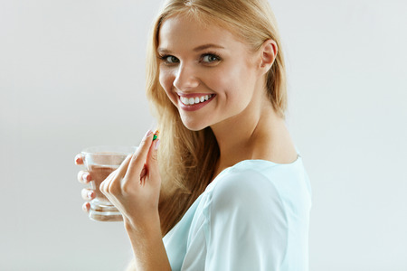 Healthy Diet Nutrition. Portrait Of Beautiful Smiling Young Woman Taking Vitamin Pill. Closeup Of Happy Girl Holding Colorful Capsule Pill And Glass Of Fresh Water. Dietary Supplement. High Resolution Banco de Imagens
