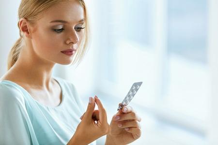 여자 복용 의학입니다. 아름 다운 젊은 여자 물집 팩 환 약을 손에 들고. 매력적인 여자 복용 복용 알 약, 정제와 함께 패키지를보고의 초상화. 건강 관 스톡 콘텐츠
