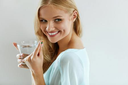 capsule: Healthy Diet Nutrition. Portrait Of Beautiful Smiling Young Woman Taking Vitamin Pill. Closeup Of Happy Girl Holding Colorful Capsule Pill And Glass Of Fresh Water. Dietary Supplement. High Resolution Stock Photo