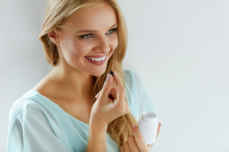 Mujer que toma la medicina. Sonriente chica hermosa toma el medicamento, sosteniendo la botella con pastillas en la mano. Sana feliz femenina de la consumición de la píldora. Vitaminas y suplementos, nutrición concepto de dieta. Alta resolución Foto de archivo - 69595908
