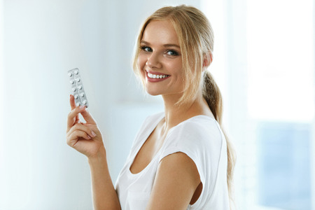 Medicine. Beautiful Smiling Woman Holding Blister Pack With Pills In Hand. Closeup Portrait Of Healthy Happy Girl With Tablets, Medicament Blister Pack At Home. Health Care Concept. High Resolution Stock fotó - 69595909