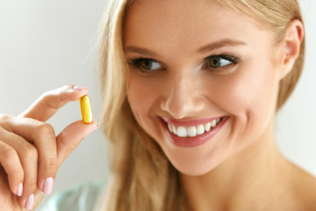 Vitamin And Supplement. Beautiful Smiling Woman Holding Fish Oil Capsule In Hand. Portrait Of Happy Girl Taking Pill With Cod Liver Oil, Omega-3. Diet Nutrition And Healthy Eating Lifestyle Concept.