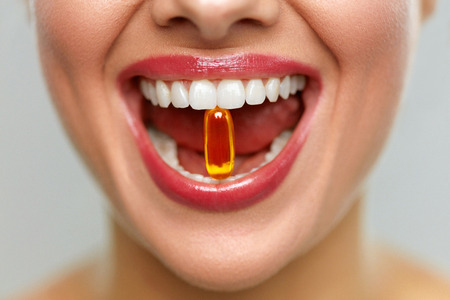 Vitamins And Food Supplements. Close Up Of Beautiful Woman Opened Mouth Holding Fish Oil Pill In White Teeth. Smiling Girl Holding Capsule With Omega-3 Between Teeth. Healthy Diet Nutrition Concept Reklamní fotografie