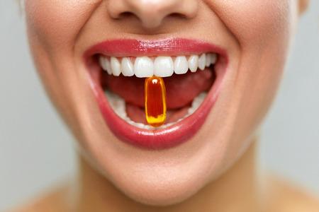 Witaminy i suplementy diety. Zamknij Się Pięknej Kobiety Otwarte Usta Gospodarstwa Pigułki Oleju Rybnego W Białych Zęby. Uśmiechnięta dziewczyna gospodarstwa kapsułka z Omega-3 między zębami. Pojęcie diety zdrowej diety Zdjęcie Seryjne