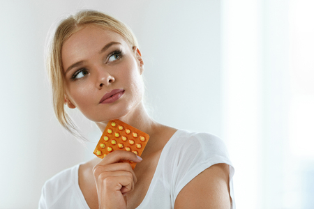 Vrouw met pil. Gezonde Beautiful Girl Holding Blister Pack Met orale anticonceptiepillen in de hand en denken moet ze Take A Pill. Medicine, Health Care Concept. Hoge resolutie