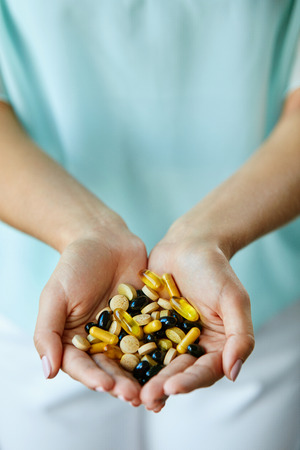 Vitamins And Supplements. Closeup Of Woman Hands Holding Variety Of Colorful Vitamin Pills. Close-up Handful Of Medication, Medicine Tablets, Capsules. Healthy Diet Nutrition Concept. High Resolution Stock Photo