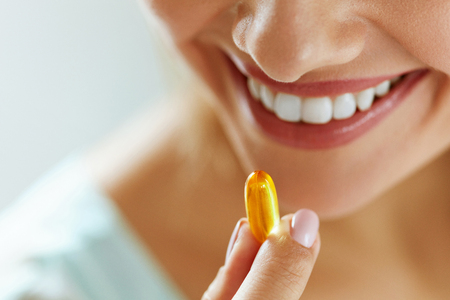 witaminy: Vitamin And Supplement. Closeup Of Beautiful Young Woman Taking Yellow Fish Oil Pill. Female Hand Putting Omega-3 Capsule In Mouth. Healthy Eating And Diet Nutrition Concepts. High Resolution Image