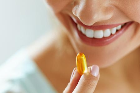 Vitamin und Ergänzung. Nahaufnahme der schönen jungen Frau, die Gelb Fischöl Pille. Weibliche Hand, die Omega-3-Kapsel im Mund. Gesunde Ernährung und Diät Diät-Konzepte. Hohe Auflösung Bild Standard-Bild