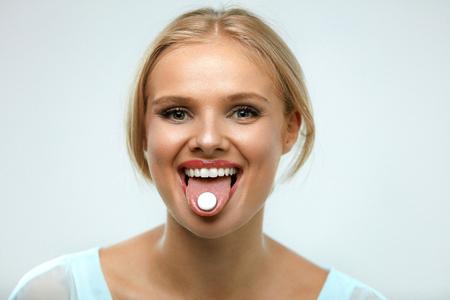 lengua afuera: Vitaminas y pastillas. Hermosa mujer sonriente que toma la medicina, sostiene la píldora en la lengua hacia fuera. Retrato de la muchacha alegre sana sostiene la píldora con la boca abierta. Suplementos, concepto de la salud. Alta resolución