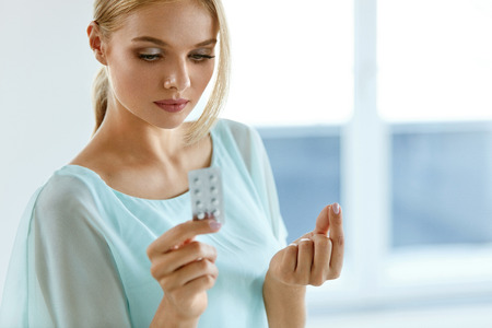 Woman Taking Medicine. Beautiful Young Woman Holding Blister Pack With Pills In Hand. Portrait Of Attractive Girl Taking Pill, Looking At Package With Tablets. Health Care Concept. High Resolution