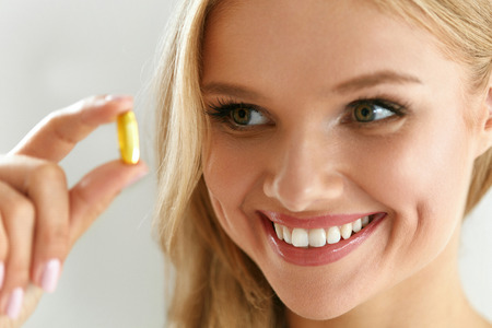 vitamin pill: Vitamin And Supplement. Beautiful Smiling Woman Holding Fish Oil Capsule In Hand. Portrait Of Happy Girl Taking Pill With Cod Liver Oil, Omega-3. Diet Nutrition And Healthy Eating Lifestyle Concept.
