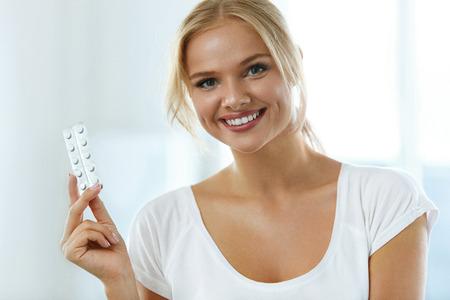 Geneeskunde. Mooie glimlachende vrouw die Blister Pack Met Pillen In Hand. Close-up portret van gezonde Gelukkig Meisje Met Tabletten, Geneesmiddel Blister Pack Thuis. Health Care Concept. Hoge resolutie Stockfoto