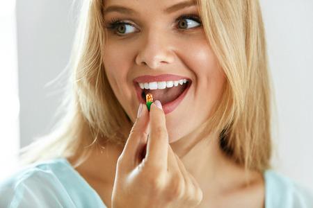 Vrouw die medicatiepil innemen. Mooi glimlachend meisje dat geneeskunde neemt. Portret van Gezonde Gelukkige Vrouwelijke Capsule Holding In Hand. Vitaminen en voedingssupplementen, dieetvoeding Concept. Hoge resolutie