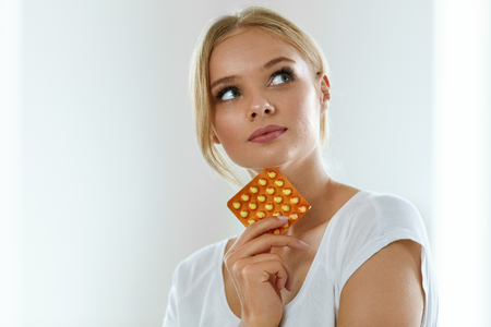 Woman With Birth Control Pills. Healthy Beautiful Girl Holding Blister Pack With Oral Contraceptive Pills In Hand And Thinking Should She Take A Pill. Medicine, Health Care Concept. High Resolution