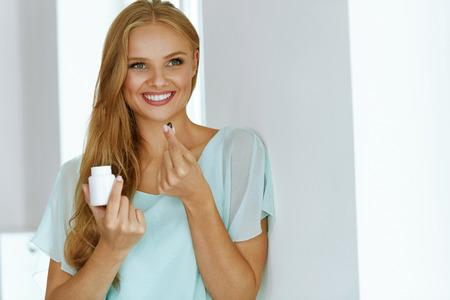 Mujer que toma la medicina. Sonriente chica hermosa toma el medicamento, sosteniendo la botella con pastillas en la mano. Sana feliz femenina de la consumición de la píldora. Vitaminas y suplementos, nutrición concepto de dieta. Alta resolución Foto de archivo