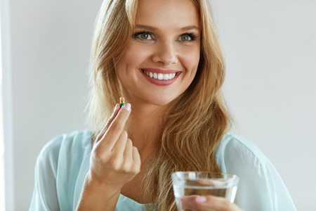 vitamin pill: Healthy Diet Nutrition. Portrait Of Beautiful Smiling Young Woman Taking Vitamin Pill. Closeup Of Happy Girl Holding Colorful Capsule Pill And Glass Of Fresh Water. Dietary Supplement. High Resolution Stock Photo