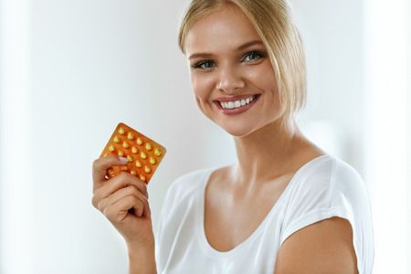 Woman With Birth Control Pills. Beautiful Smiling Girl Holding Blister Pack With Oral Contraceptive Pills. Healthy Happy Girl With Pill Package In Hand. Medicine, Health Care Concept. High Resolution