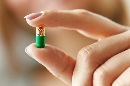 medical cure: Medicine. Closeup Of Female Hand Holding Colorful Vitamin Pill In Fingers. Close-up Woman Hand Holding Medication, Medical Capsule. Health Care, Cure Concept. High Resolution Image
