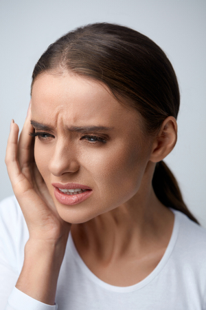 Health Care. Closeup Of Beautiful Young Woman Suffering From Terrible Strong Head Pain, Touching Her Face. Tired, Exhausted Female Feeling Stress And Having Painful Migraine, Headache. High Resolution Stock Photo