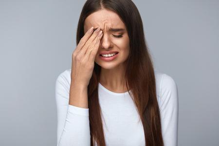 痛み。疲れて疲れてストレス女性の強い目の痛みに苦しんで。気分、頭痛、鼻の痛みを持っていると痛い目に触れる美しいの若い女性の肖像画。ヘ