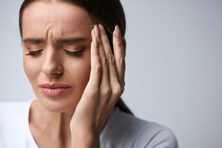 健康管理。彼女の顔に触れて強い頭のひどい痛みに苦しんで美しい若い女性のクローズ アップ。疲れた、疲れ果てた女性ストレスを感じていて、痛 写真素材