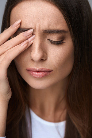 healthcare portrait: Pain. Tired Exhausted Stressed Woman Suffering From Strong Eye Pain. Portrait Of Beautiful Young Female Feeling Sick, Having Headache, Nose Pain And Touching Painful Eyes. Healthcare. High Resolution