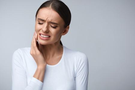 치아 통증과 치과. 아름 다운 젊은 여자 고통에서 끔찍한 고통, 손으로 뺨을 만지고. 여성 고통스러운 치 통입니다. 치과 치료 및 건강 개념입니다. 높