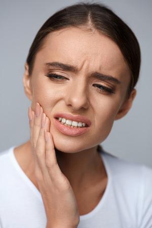 molesto: Dolor de muelas y la salud dental. Retrato de la hermosa mujer que sufre de dolor molesto dientes fuertes, tocando su cara con la mano, Sensación de dolor de muelas. Concepto de salud. Alta resolución