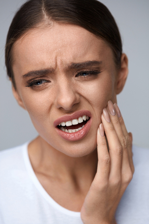molesto: Teeth Pain And Dental Health. Portrait Of Beautiful Woman Suffering From Annoying Strong Teeth Pain, Touching Her Face With Hand, Feeling Painful Toothache. Health Care Concept. High Resolution