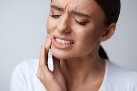 El dolor de dientes y odontología. Hermosa mujer joven que sufre de un dolor terrible dientes fuertes, Cheek Tocar con la mano. Sensación dolorosa Mujer del dolor de muelas. Cuidado dental y concepto de la salud. Alta resolución