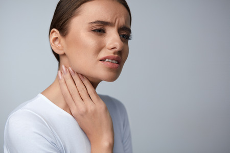 Throat Pain. Beautiful Woman Having Sore Throat, Feeling Sick. Unhappy Ill Female Suffering From Painful Swallowing, Strong Pain In Throat, Holding Hand On Her Neck. Health Concept. High Resolution Zdjęcie Seryjne