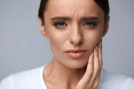 치아 문제. 여자 느낌 치아 통증입니다. 강한 치아 통증에서 고통을 아름 다운 슬픈 여자의 근접 촬영. 매력적인 여자 고통스러운 치 통입니다. 치과 건