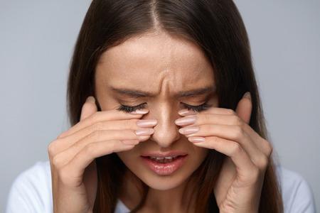 눈의 통증. 강한 눈 통증에서 고통 아름다운 불행한 여자. 손으로 피곤 고통스러운 눈을 터치 슬픈 여자 느낌 스트레스의 근접 촬영 초상화. 건강 관리,