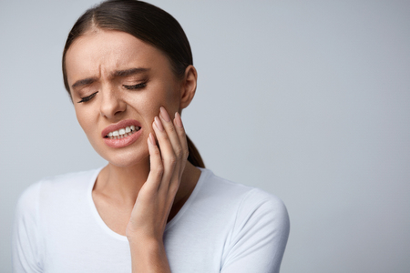 hurt: Tooth Pain And Dentistry. Beautiful Young Woman Suffering From Terrible Strong Teeth Pain, Touching Cheek With Hand. Female Feeling Painful Toothache. Dental Care And Health Concept. High Resolution