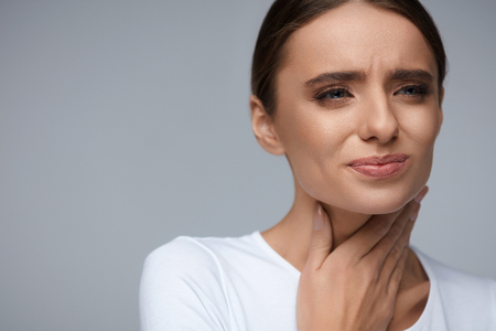 Throat Pain. Beautiful Woman Having Sore Throat, Feeling Sick. Unhappy Ill Female Suffering From Painful Swallowing, Strong Pain In Throat, Holding Hand On Her Neck. Health Concept. High Resolution Stock Photo